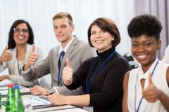 People at business conference showing thumbs up Stock Photo