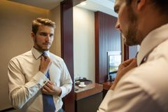 People, business,fashion and clothing concept - close up of man in shirt dressing up and adjusting tie on neck at home. royalty free stock image