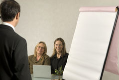 People in Business Meeting. A Boss in instructing his employees in a business meeting.  The two girls are smiling at him.  Horizontally framed shot Stock Photography