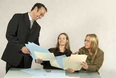 People in Business Meeting. Three people are in a business meeting.  They are smiling and looking at some pieces of paper .  The women are sitting and the man is Royalty Free Stock Photos