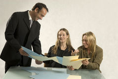 People in Business Meeting. Three people are in a business meeting.  They are smiling and looking at pieces of paper in front of them.  Horizontally framed shot Stock Photography