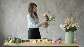 People, business, sale and floristry concept - happy smiling florist woman making bunch at flower shop, bouquet with
