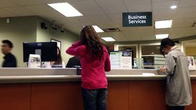 People at business service counter talking to the teller stock footage