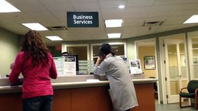 People at business service counter talking to the teller stock video footage