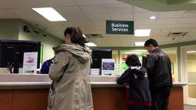 People at a business service counter talking to the teller stock video footage