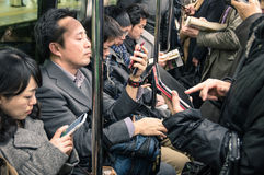 People busy with smartphones and tablets in Tokyo subway train. TOKYO -MARCH 2, 2015: people busy with smartphones and tablets in the underground train. The Stock Images