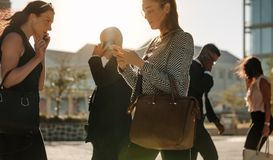 People busy using mobile phone while walking on street to office. Men and women using mobile phone while commuting to office on a crowded street with sun flare stock photography