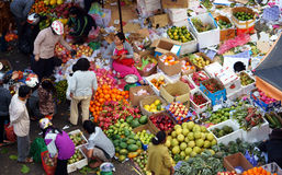 People buy and sell fruit at market. DA LAT, VIET NAM- FEBRUARY 8, 2013 Royalty Free Stock Photos