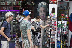 People buy souvenirs near Queen portrait Royalty Free Stock Image