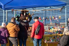 People buy wooden toys at the popular farmers market at the Naplavka riverbank in Prague. PRAGUE, CZECH REPUBLIC - NOVEMBER 17, 2018: People buy wooden toys at stock photos