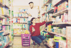 People buying detergents for house. Glad couple buying detergents for house in the shopping mall Royalty Free Stock Photo