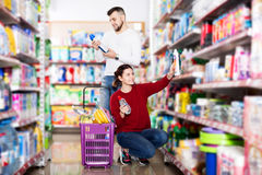 People buying detergents for house. Glad couple buying detergents for house in the shopping mall Royalty Free Stock Image