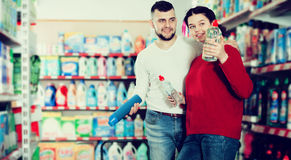 People buying detergents for house. Happy couple buying detergents for house in the shopping mall Royalty Free Stock Image