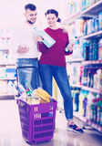 People buying detergents for house. Happy people buying detergents for house in the shopping mall Royalty Free Stock Photography