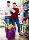 People buying detergents for house. Happy people buying detergents for house in the shopping mall Stock Image