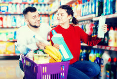 People buying detergents for house. Smiling people buying detergents for house in the shopping mall Royalty Free Stock Image