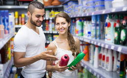 People buying detergents  in the shopping mall. Happy european people buying detergents for house in the shopping mall Royalty Free Stock Images