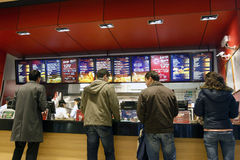 People buying fast food products. Customers are buying fast food products inside a KFC (Kentucky Fried Chicken) restaurant Stock Photos