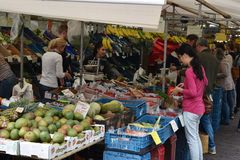 Fruits and vegetables market. People buying fruits and vegetables at market in Delft Netherlands. Woman opening her wallet and mango boxes in the front Royalty Free Stock Image
