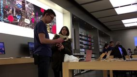 People buying iphone and paying credit card stock footage