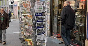 People buying magazines - French and International newspapers stock video footage