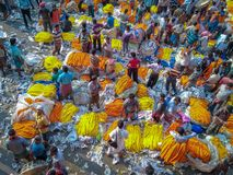 People buying and selling flowers and garlands at the flower market near mullick royalty free stock photo