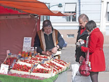 People buying strawberries. Man and woman buying strawberries on the market square in Helsinki. Finland Royalty Free Stock Images