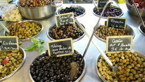 People buying at street market flowers fruits and vegetables in Aix-en-Provence France. Large variety of fresh olives and olive oil on rustic typical French stock video footage