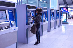 People buying ticket automatic machine. A girl buying ticket on the automatic ticket machine in the hall of Beijing South Railway Station Stock Image