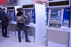People buying ticket automatic machine. Man and woman buying ticket on the automatic ticket machine in the hall of Beijing South Railway Station Stock Images