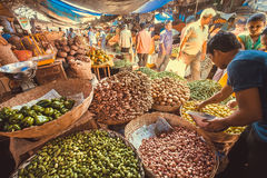 People buying vegetables in a big market with peppers, ginger and potatoes Stock Images