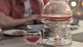 People in the cafe, transparent teapot on a table with candles heated. HD stock footage