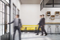 People in cafe with a yellow sofa royalty free stock images