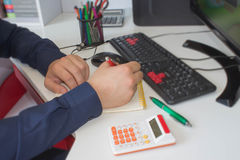 People calculate about and note data cost at home ,Finance managers task,Concept business and finance. Man hand with pen, calculator and computer on wooden royalty free stock photography