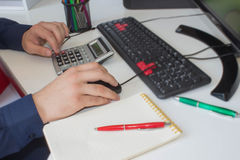 People calculate about and note data cost at home ,Finance managers task,Concept business and finance. Man hand with pen, calculator and computer on wooden stock images