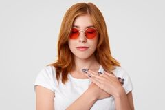People and calmness concept. Pretty young female in stylish sunglasses, keeps eyes closed and hands on heart, touched by good word stock images