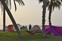People camping on the beach with palm trees Malaga Spain stock photography