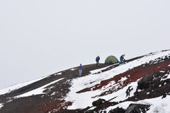 People camping at the Cotopaxi volcano near to Quito, Ecuador. People arming a tent over the Cotopaxi volcano during a snowing day in Ecuador stock images