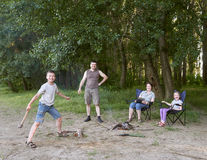People camping in forest, family active in nature, kindle fire, summer season Stock Photo