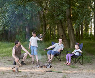 People camping in forest, family active in nature, kindle fire, summer season Stock Images
