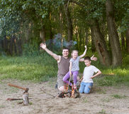 People camping in forest, family active in nature, kindle fire, summer season Royalty Free Stock Photos