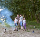 People camping in forest, family active in nature, kindle fire, summer season Stock Photos
