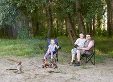 People camping in forest, family active in nature, kindle fire, summer season Stock Photography