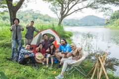 People camping showing thumb up. Excited young people enjoying their holiday camping together by a lake showing thumb up Royalty Free Stock Photography