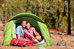 People camping in tent - happy backpacking couple. In forest. Campers smiling happy outdoors in forest. Happy multiracial couple having fun relaxing in outdoor royalty free stock photo