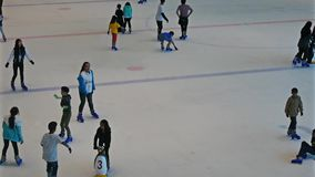 People can seen playing ice skating at a public ice skating rink. stock footage