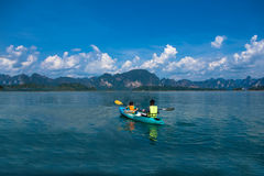 People canoeing on scenic lake in summer, THAILAND Royalty Free Stock Image