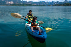People canoeing on scenic lake in summer, THAILAND Stock Image