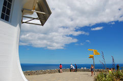 People at Cape Reinga lighthouse direction signs stock photo