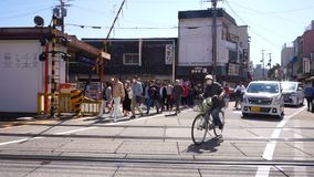 People and car  cross the railway crossing after the train barriers open. Kyoto, Japan - April 28 : People and car  cross the railway crossing after the train stock video footage